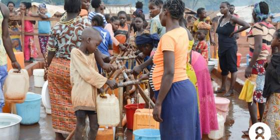 18 juillet 2019 - Des familles viennent remplir leurs bidons à un point d'eau. Le réseau gravitaire installé par Oxfam per-met de fournir de l'eau aux 50 000 déplacés du site PK3 de Bria, dans le centre de la RCA. © Aurélie Godet/Oxfam