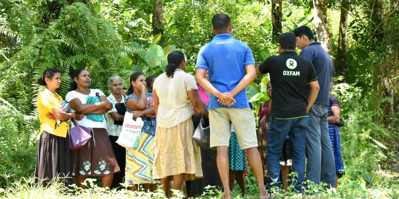 Oxfam team members in discussion with members of a small village in Ratnapura