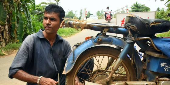 Sri Lankan man repairs a motorcycle