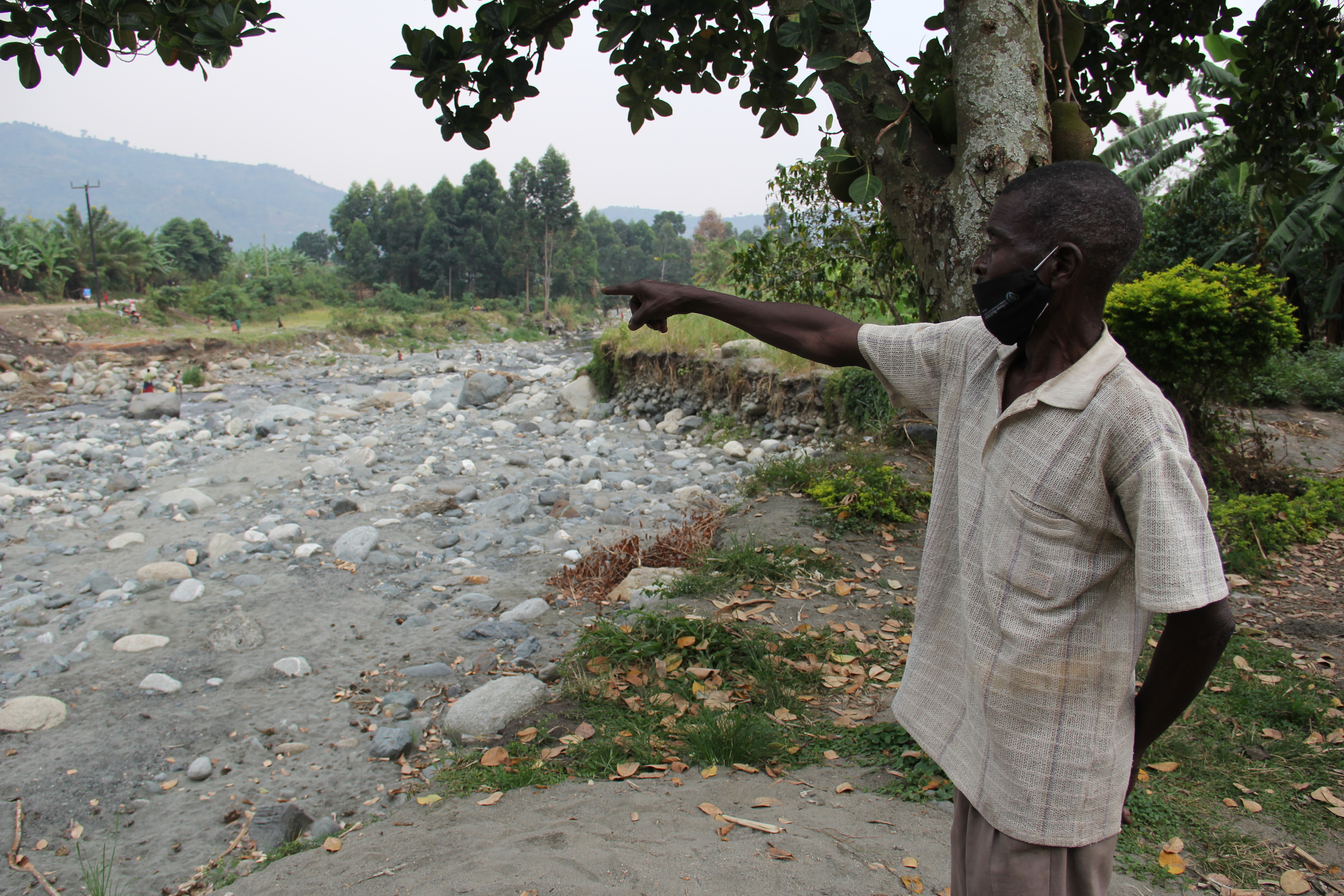 Mbusi points to where his home once was, but now lies flood debris.