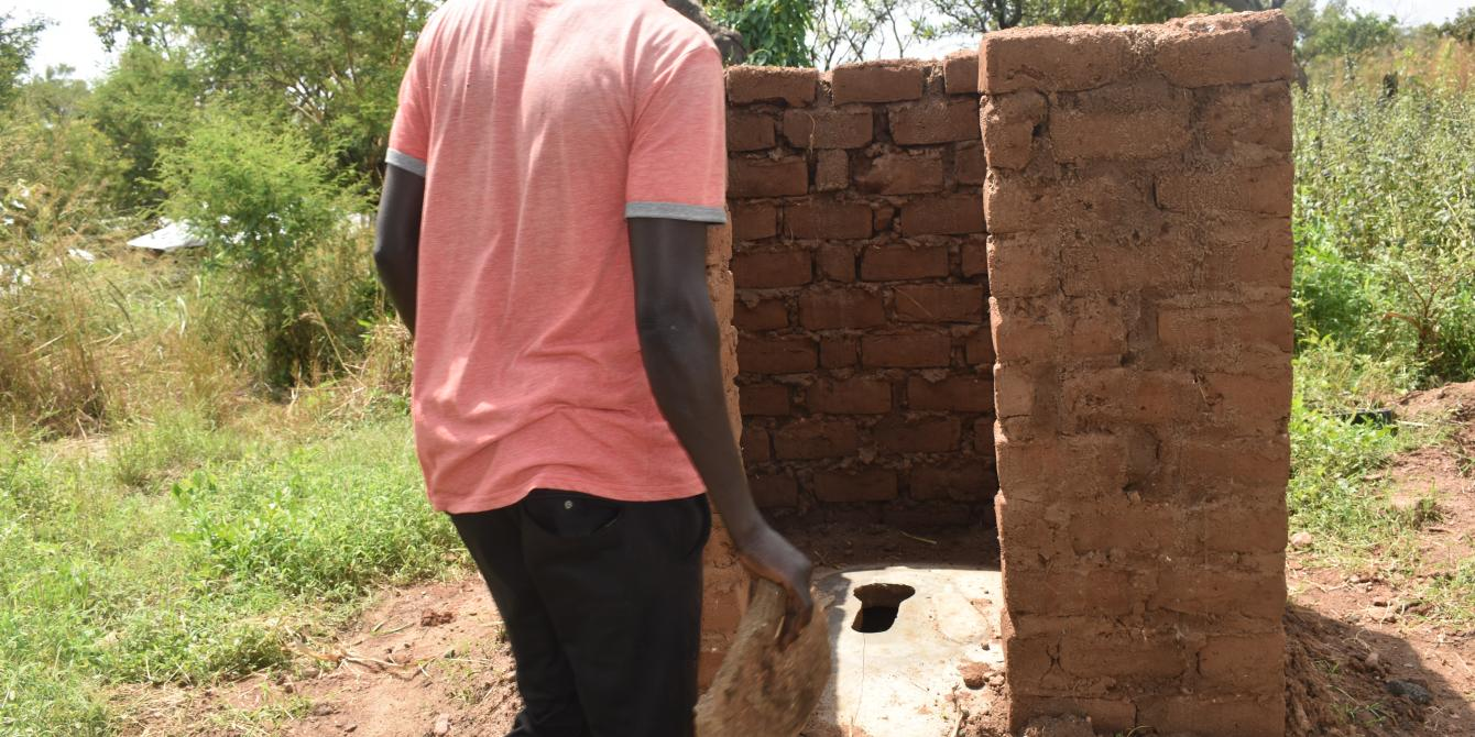 A refugee stands infront of a latrine nearing completion. credit: Oxfam