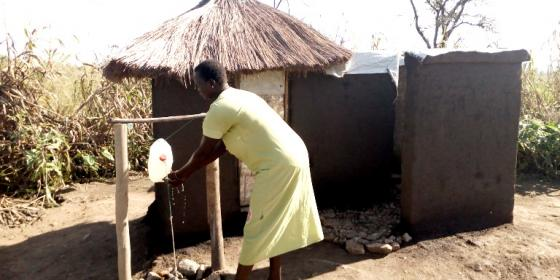 Betty 31 years and single mother of 6 children demonstrates hand-washing at her home latrine Photo: Robert Ariaka/Oxfam