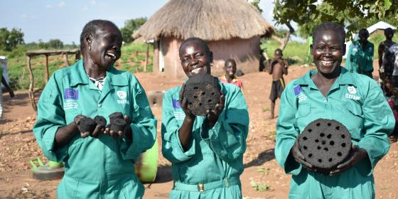 Refugee women holding briquettes that they made. Photo - Oxfam
