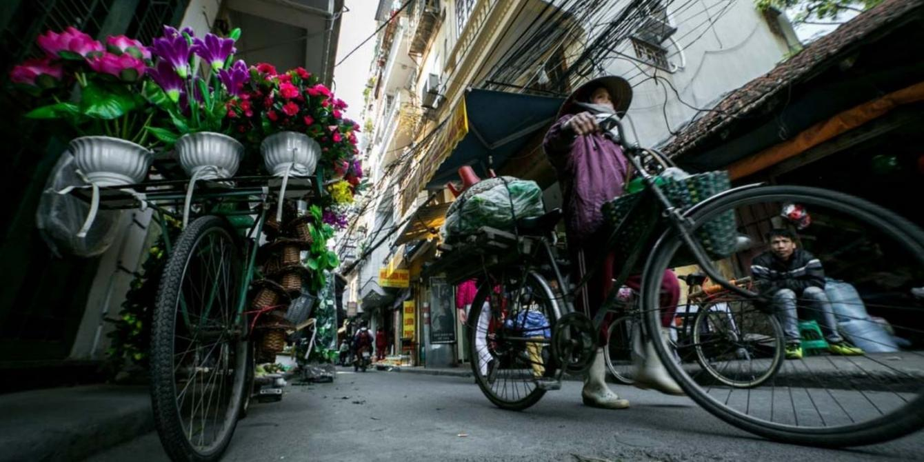 A woman cycles to work in Hanoi. Credit: Dewald Brand, Miran for Oxfam