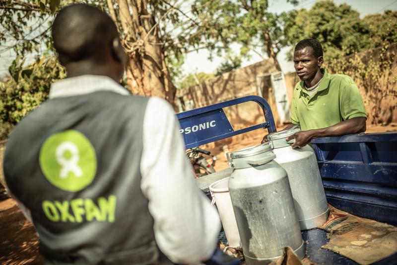 Ibrahim Lido déchargeant des fûts de lait à Kossam de L'Ouest une usine de tri de collecte de dérivés du lait à Bobo Diulasso au Burkina Faso. Crédit : Pablo Tosco / Oxfam