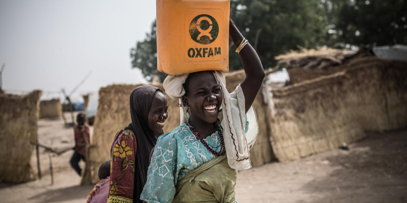 Two women carry water in Oxfam jerry cans at Muna Garage, an IDP camp in Nigeria. Credit: Pablo Tosco / Oxfam