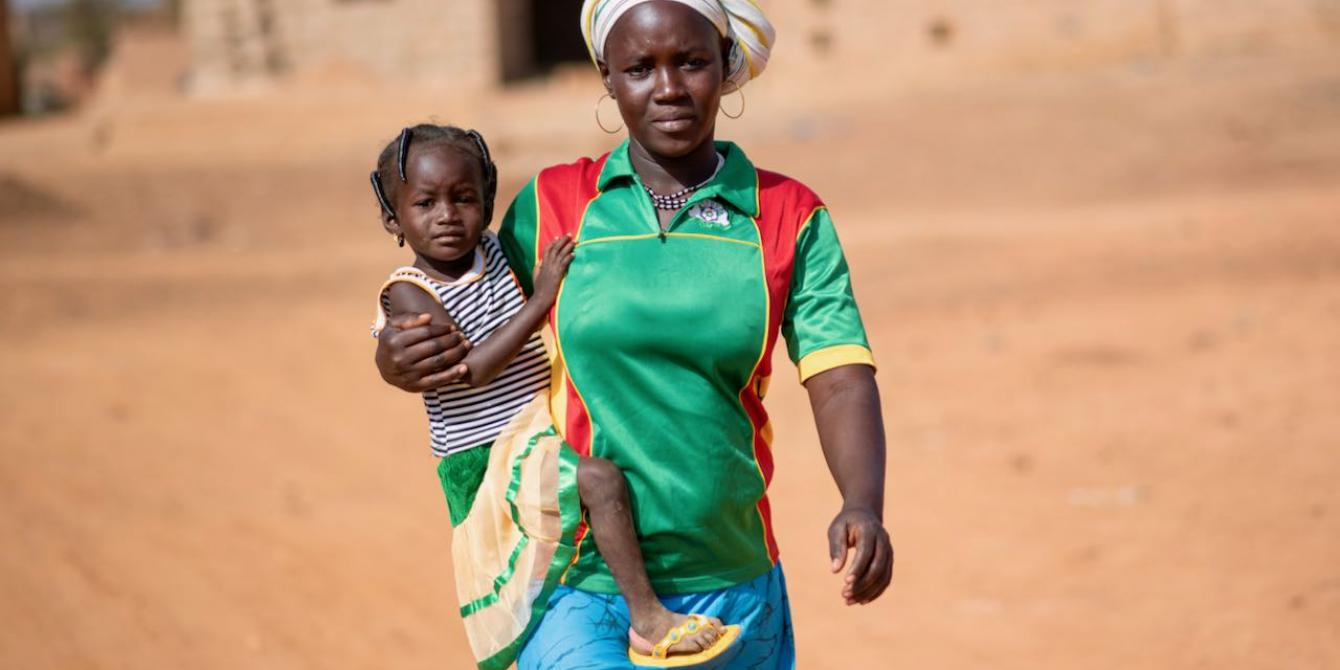 Mariam, 25, holds her daughter. She fled her village in Dablo, in north-central Burkina Faso, leaving behind her dream of studying. Credit: Sylvain Cherkaoui / Oxfam