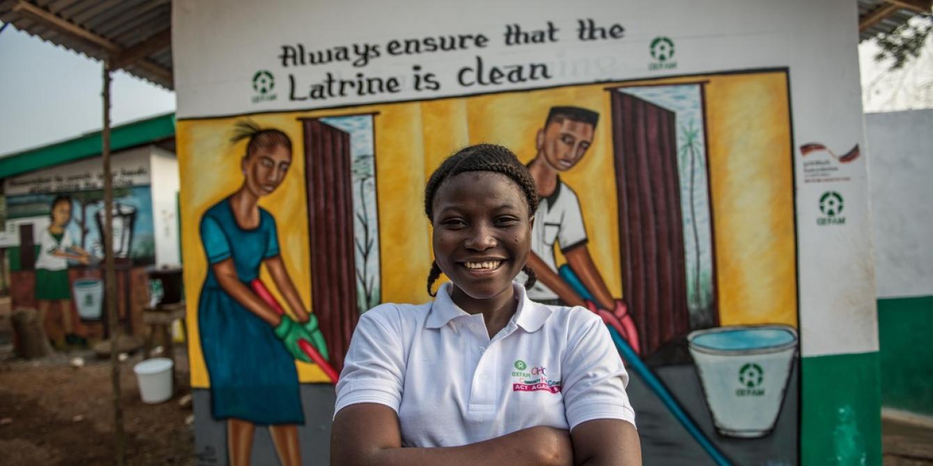 Fatima pose devant une latrine nouvellement construite par Oxfam au lycée Educaid à Port Loko, Sierra Leone.