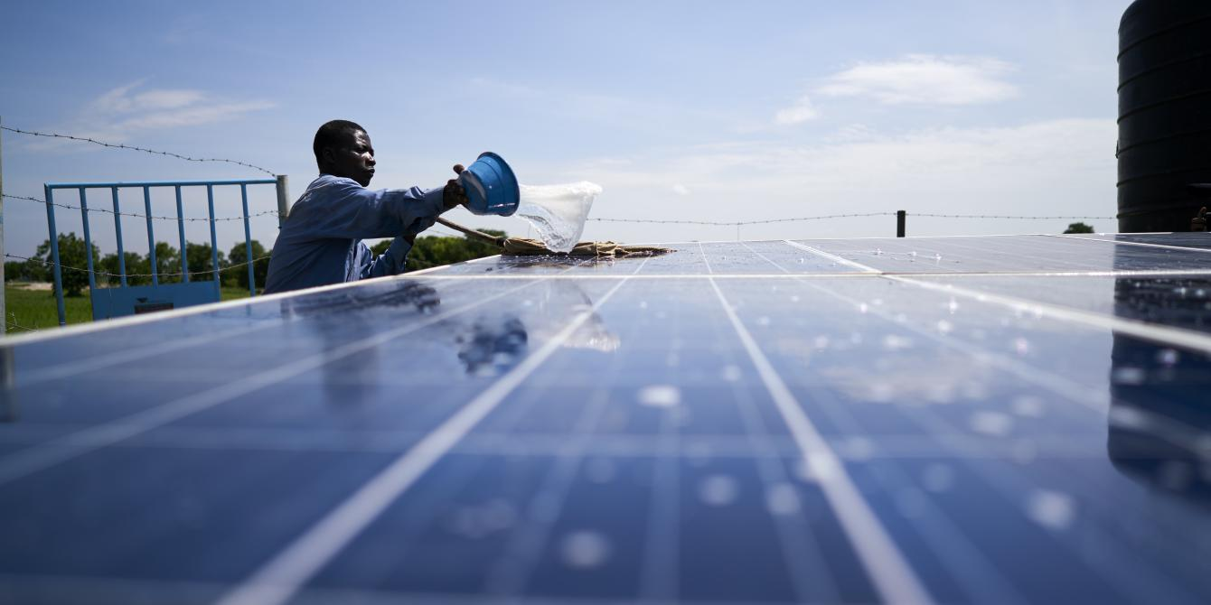 Joshua maintains the solar panels for his new irrigation system in Kpatua, Ghana, an Oxfam initiative.