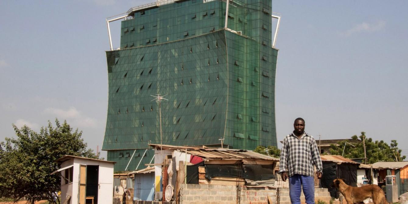 Peter Akmtter travaille dans le gratte-ciel qui se dresse derrière lui dans la capitale du Ghana, Accra. À l'instar de nombreux ouvriers, il vit avec sa famille dans des maisons de fortune sur les sites de construction ou alentour. Crédit photo : Lotte Ærsøe/Oxfam